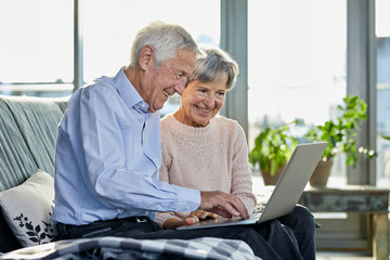 Senior couple sitting together on couch using laptop