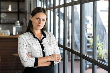 Portrait of attractive businesswoman in front of windows
