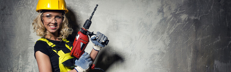 Attractive builder woman with a drill horizontal image