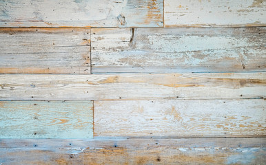 Aged faded reclaimed wood surface with painted boards lined up. Vintage wooden planks on a wall or floor.