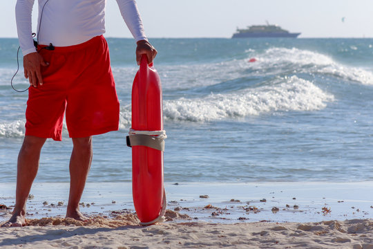 Lifeguard holding rescue buoy in the beach