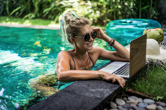 Attractive young female sitting in the swimming pool and working on a laptop. .Beautiful young female freelancer blogger working on laptop from the pool. work on vacation.