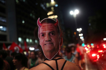 """A woman wears a mask depicting Brazil's president Jair Bolsonaro face that reads """"enemy of workers and retirees"""" on the back of her head during a protest against him in Sao Paulo"""