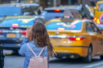 Tourist young girl taking a picture with her cell phone in Downtown New York