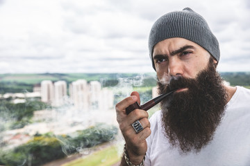 Stylish bearded man smoking pipe looking at the horizon from the top of a tall building.