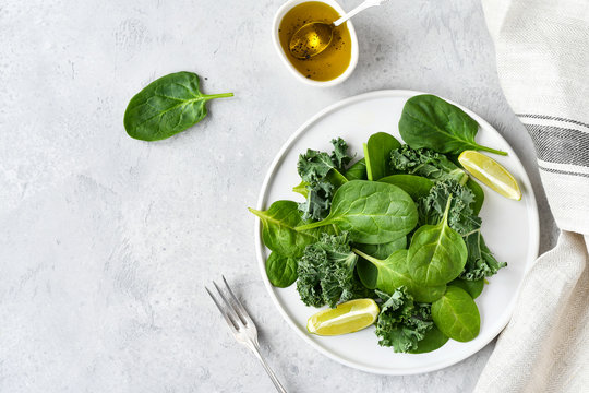 green salad of organic spinach and kale leaves with lemon juice and olive oil. diet menu concept, healthy food, save space, selective focus, light background,