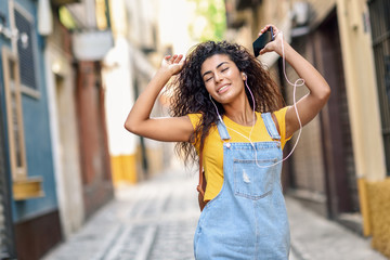 Attractive African girl listening to music with earphones outdoors.