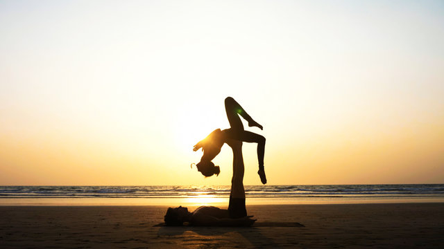 Silhouette of fit sporty couple practicing acrobatic yoga with partner together on the beach in slow motion. Female acrobat balancing on feet of her partner in fylfot shape