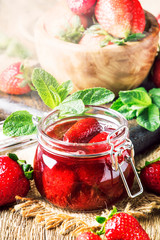 Strawberry confiture with whole berries, vintage wooden kitchen table background, summer preservation of jam and cooking, selective focus