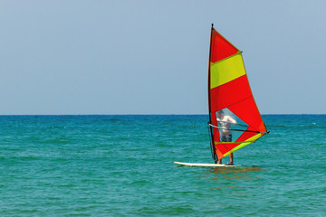 Windsurfing on the background of the sea landscape and clear sky. Windsurfer male go in for sports, copy space