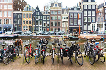 Street in Amsterdam, yachts on the canal and bicycle parking in the foreground close