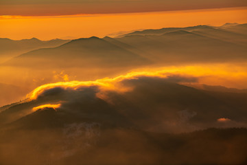 Mountain landscape with winter fog at sunse of Ceahlau, Romaniat