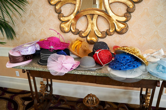 ladies dress hats piled on a table