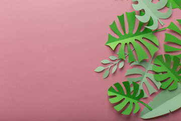 Pink background with green leaves of paper on the right side, minimalism