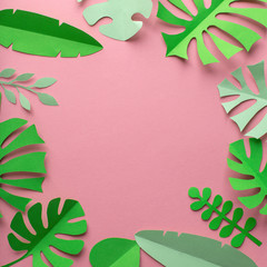 Pink background with green leaves of paper in a circle, minimalism