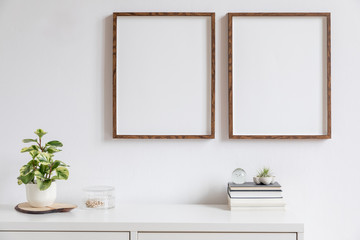 Minimalistic home decor of interior with two brown wooden mock up photo frames above the white shelf with books, beautiful plant in stylish pot and home accessories. White wall. Concept of mockup.