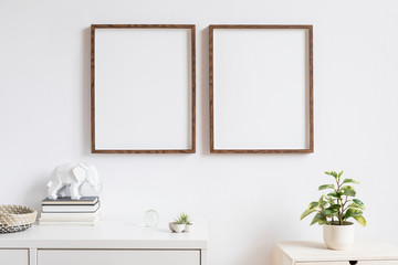 Elegant home interior with two brown wooden mock up photo frames above the white shelf with books, air plants, wooden basket and geometric elephant figure. Modern concept of white room decor.