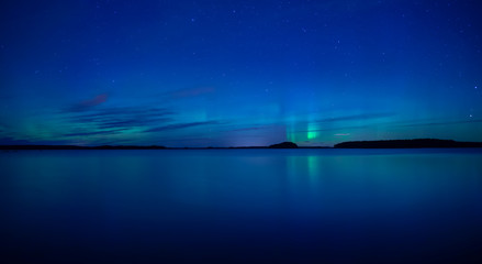 Wall Mural - Northern lights dancing over calm lake after the sunset under the blu time