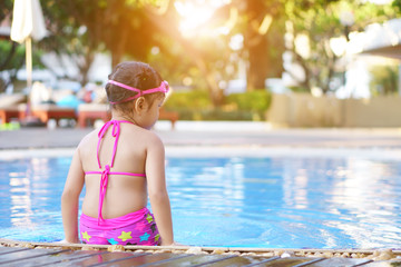 Asian child cute or kid girl backside wear goggles and bikini sit on swimming pool with happy fun in water park for refreshing and relax with exercise on summer holiday travel at hotel on sunlight