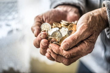 Pensioner man holding in hands euro coins. Theme of low pensions Wall mural