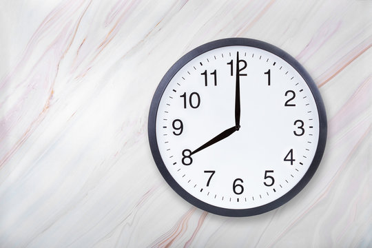 Wall clock show eight o'clock on marble texture. Office clock show 8pm or 8am on marble texture with natural pattern