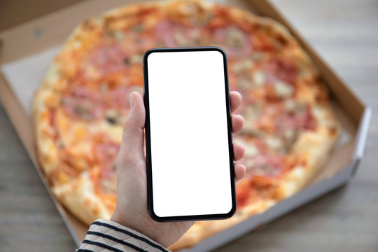holding phone with isolated screen above pizza box