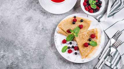 Delicious Crepes Breakfast on gray concrete table background. Orthodox holiday Maslenitsa. Pancakes with berry black currant, raspberry, jar of honey and mint. White cup of tea. Banner