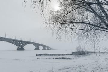 Classic winter landscape - a bridge in the fog on a frozen river
