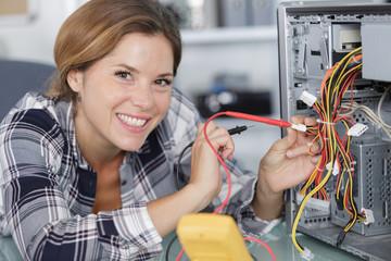 computer repairwoman using multimeter