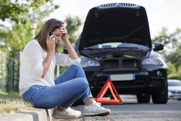 woman on the telephone beside her broken down car