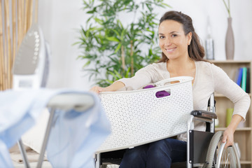 happy woman in wheelchair carrying basket of laundry