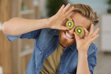 man playing with kiwis eyes
