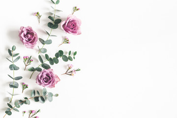 Flowers composition. Pattern made of eucalyptus branches and rose flowers on white background. Flat...
