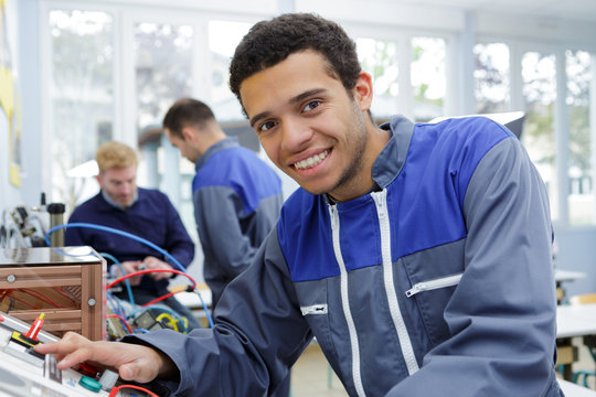 portrait of young technician at controls of machine
