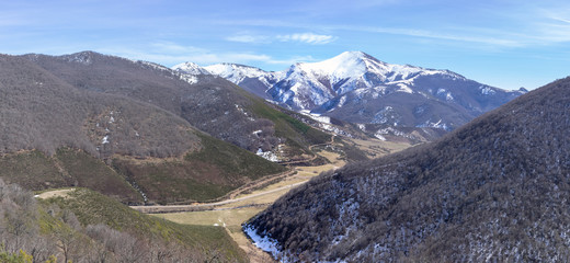 Views of the snowy mountains with a river in the valley, near Buron in Leon, Spain.