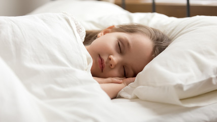 Calm kid girl sleeping in bed covered with warm duvet