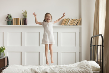 Happy funny child girl jumping on bed alone feeling joy