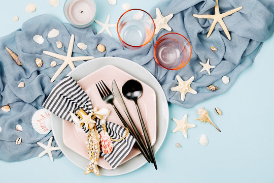 Tableware and sea decorations for serving a festive table. Plates, wine glasses and cutlery on blue background. Summer concept. Flat lay, top view