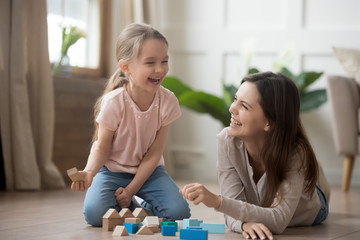 Happy mom and kid daughter laughing playing with wooden blocks