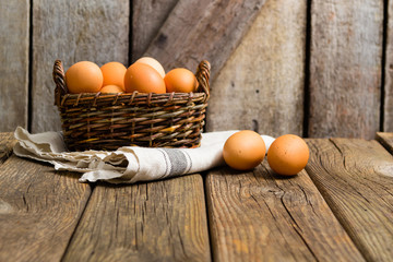 basket of eggs, old weathered wooden background