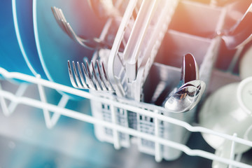 Open dishwasher with clean shine dishes and forks, spoons, cutlery. Concept water saving