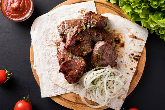 Grill, barbecue meat on wooden board.  Veal shish kebab.  Veal kebab. Top view
