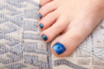 A young Caucasian woman paints her toenails.