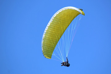 Paraglider flying yellow wing
