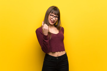 Woman with glasses over yellow wall inviting to come with hand. Happy that you came