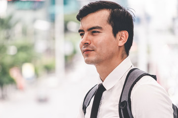 man standing outdoors with backpack in summer city