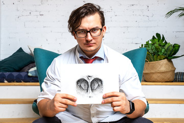 Serious professional  psychologist showing paper with Rorschach inkblot
