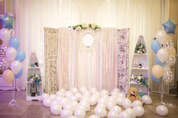 close up photo of a wooden backdrop decorated with tule and flowers surrounded by white and blue baloons and other decor objects at a christening party with marine motives