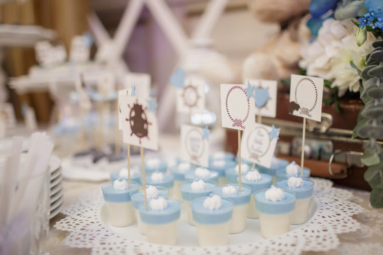 blue and white christening candy bar: close up photo of pana cotta with sticks with messages