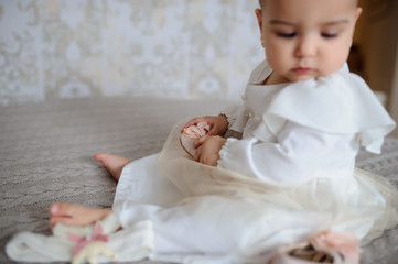 lateral view of a cute baby girl in a white dress on a gray blanket at home